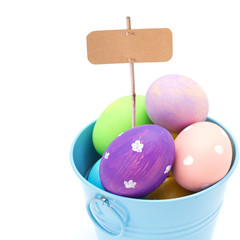 Easter eggs ib bucket with empty tag  isolated on white