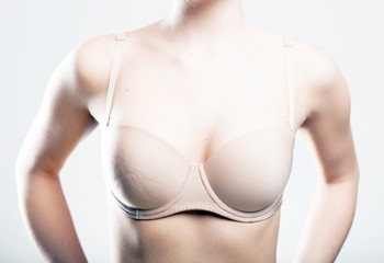 Skin-colored bra, breast of young woman