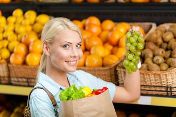 Choosing grape girl hands bag with fresh vegetables