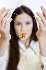 Woman holding necklace with yellow sapphire at jeweler's shop