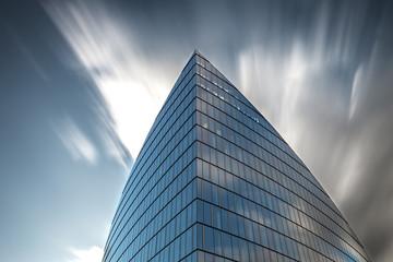 Hochhaus Fensterfront mit schnell ziehenden Wolken abstrakt
