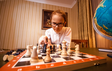 Wide angle portrait of smart girl make move on chess board