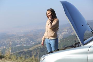 Woman on the phone beside her crash breakdown car