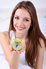 Young beautiful woman with alarm clock in bedroom