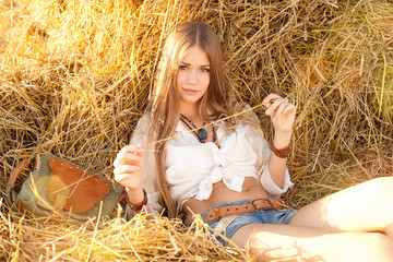 Beauty woman relaxing in the straw in field