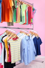 Different clothes on hangers, on pink background
