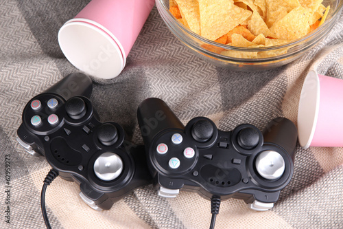 Black game controllers and bowl with snacks