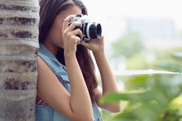 Young girl taking photographs outside