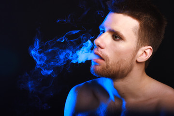 Close up portrait of young man smoking cigarette