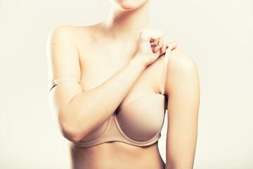 Woman holding bra strap, natural beauty