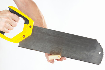 Hand  of a workman sawing a wooden block with a hacksaw