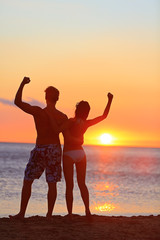 Fitness couple cheering at beach sunset