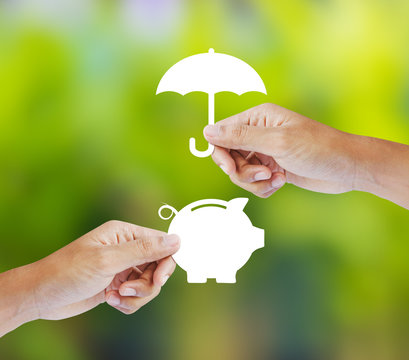 Hand holding a paper  piggy bank and umbrella, Insurance concept