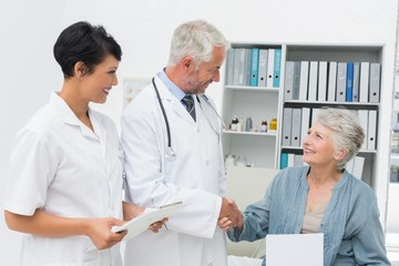 Smiling female patient and doctor shaking hands
