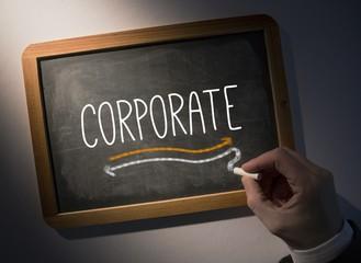 Hand writing Corporate on chalkboard