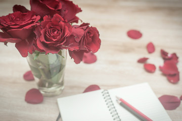 retro image in soft focus, red roses and notebook with pencils o