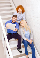team with tablet pc computer sitting on staircase