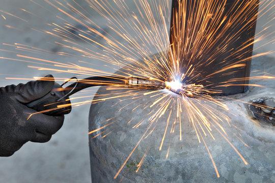 Arc welding of a steel, welder hands in gloves and tool