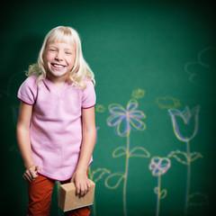 kleines Mädchen malt mit Kreide auf Wand