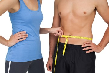 Mid section of a fit woman measuring mans waist