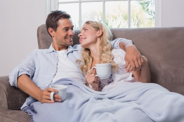 Relaxed loving young couple with coffee cups in living room