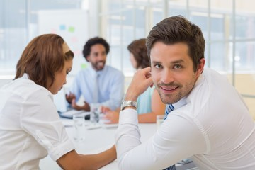 Smiling young businessman with colleagues in meeting