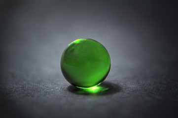 Green marble ball with reflection.
