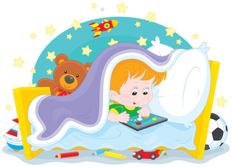 Boy playing on a tablet under a blanket in his bed