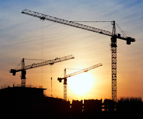 Silhouettes of construction cranes against the evening sky