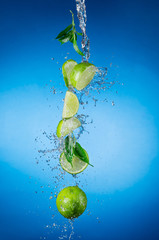 Wall Mural - Pieces of limes in water splash