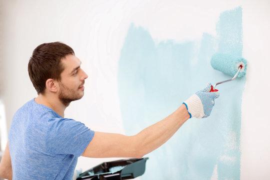 smiling man painting wall at home