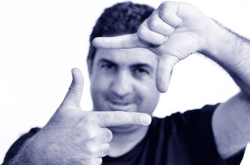 Happy mature man creating frame with fingers