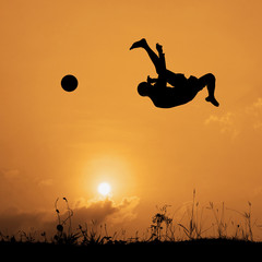 Silhouette boy jumping to kick the ball on the sky.