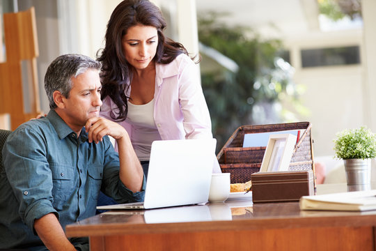 Worried Hispanic Couple Using Laptop On Desk At Home