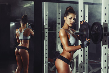 Wall Mural - athletic young sexy girl sets weight on barbell in the gym