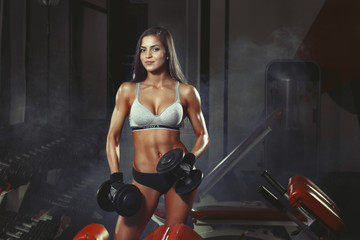 athletic girl doing a fitness workout with dumbbells in the gym