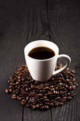 cup of coffee and coffee beans over dark background