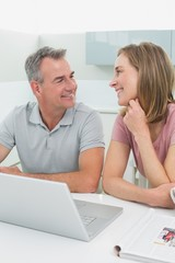 Cheerful couple using laptop in kitchen
