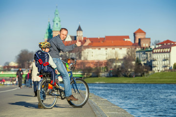 Walk on bike. Father with son cycling in city