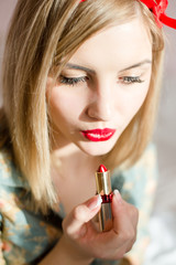 seductive young blonde pinup woman applying red lipstick