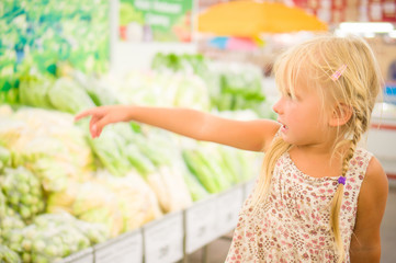 Adorable girl near shelf with vegetables at supermarket