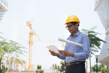 466905bb136 indian male engineer reading plans with construction background ...
