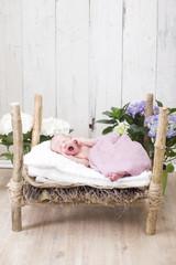 Newborn Baby schläft in einem kleinen Holzbett