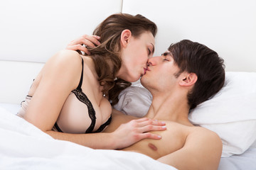 Intimate Couple Kissing In Bed
