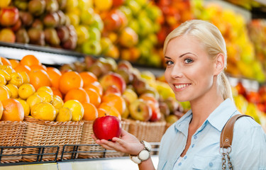 Girl at the shop choosing fruits and vegetables