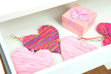 Gift and heart in open desk drawer close up