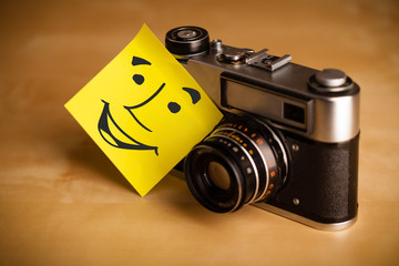 Post-it note with smiley face sticked on a photo camera