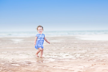 Beautiful little girl running on a beach at sunset