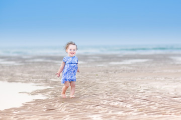Laughing toddler girl in a blue dress running at a beach
