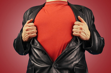 Man opens jacket showing red t-shirt
